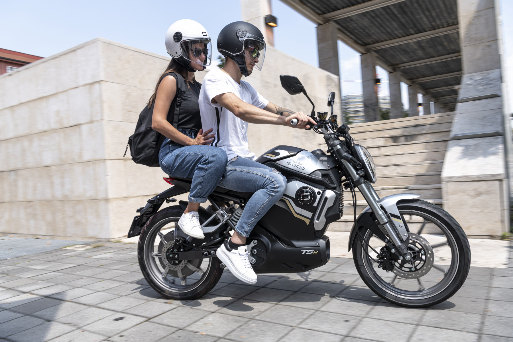 Super Soco TSx electric motorcycle being ridden with a pillion passenger
